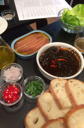 The writer's meal included anchovies and baby squid in their own ink, served with sides of bread and small bowls of salad greens, chopped onions and peppers.